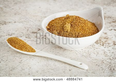 small ceramic bowl of unrefined coconut palm sugar against a ceramic tile background with a spoon