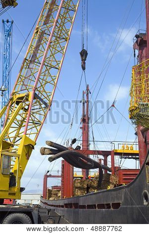 Dockside crane unloading steel rods from a freighter at Limassol Cyprus