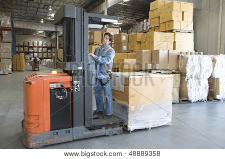Full length of a man operating forklift truck in distribution warehouse