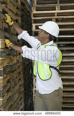 Side view of a man inspecting wooden pallets in distribution warehouse