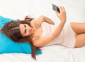brunette woman on her bed taking selfy onher phone