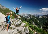 pic of breathtaking  - Young ladies with backpacks taking a pictures with Alps on the background - JPG
