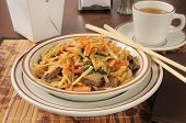 pic of lo mein  - A bowl of beef lo mein with a cup of tea - JPG