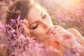 Beauty Girl Portrait. Sensual Woman Lying on a Meadow with Violet Flowers. Beautiful Woman Enjoing N