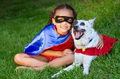 image of blue heeler  - Pretty mixed race girl hugging her pet  with both dressed up in super hero costumes - JPG