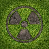 pic of nuclear disaster  - Contaminated soil concept with a green grass and the radio active symbol embosed in the ground exposing the poisoned earth as an icon of environmental disaster after a nuclear disaster and the dangerous fallout that lingers on - JPG