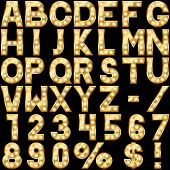 foto of marquee  - Golden alphabet with show lamps isolated on black background - JPG