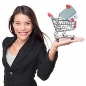 Real estate agent selling home holding mini house in shopping cart. Female realtor in business suit