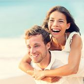 Love - Happy couple on beach having fun piggyback ride outdoor smiling happy laughing together on ro