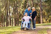 foto of mother law  - caring couple taking their disable senior mother for a walk at the park - JPG