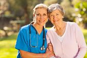 stock photo of retirement age  - mid age medical nurse and senior patient outdoors - JPG