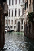 Narrow canal with gondolas in Venice Italy