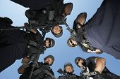 foto of policeman  - Low angle portrait of confident policemen with guns standing against sky - JPG