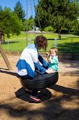 picture of tire swing  - A son and his mom share a tire swing at the playground of a park in Oregon.