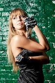 stock photo of sado-masochism  - beautiful woman with an steel chain on the background wall - JPG