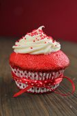 stock photo of red velvet cake  - Red velvet cupcake with a red ribbon on a wooden table - JPG