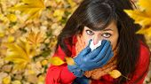 stock photo of snot  - Sick sad woman with flu or cold crying and blowing her nose with a tissue in autumn windy day with leaves flying around - JPG