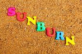 image of sunburn  - The word sunburn written in alphabet letters on a sand background - JPG