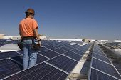 picture of electrical engineering  - Electrical engineer among solar panels at solar power plant - JPG