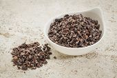 image of ceramic bowl  - small ceramic bowl of  raw cacao nibs  against a ceramic tile background with a copy space - JPG