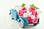 stock photo of carnations  - Old antique toy truck carrying pink carnation and lilacs flowers - JPG