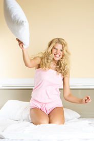stock photo of pillow-fight  - beautiful young woman at home in bed having fun and throwing a pillow at us - JPG