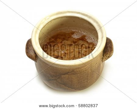 Unsolidified fresh lard with pork scratchings in earthen bowl on white background