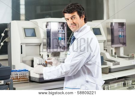 Portrait of confident male scientist using urine analyzer to test samples in medical lab