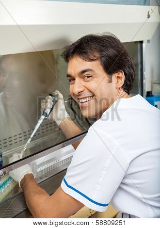 Portrait of happy young researcher filling chemical in testtube at laboratory