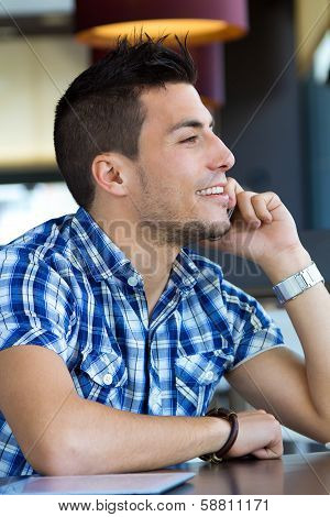 Young Man Talking On The Phone In Cafe