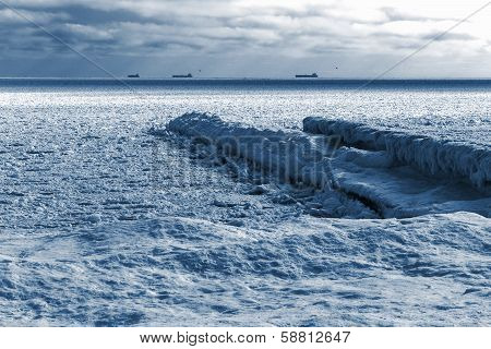 Winter Landscape. Sea Covered Blocks Of Ice On The Horizon Are Ships At Anchorage