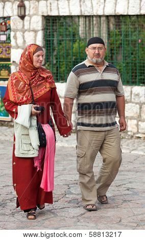 SARAJEVO, BOSNIA AND HERZEGOVINA - AUGUST 13, 2012: Muslim couple walk on Bascarsija, the old town. Sarajevo has a mixture of muslim, catholic and orthodox population.