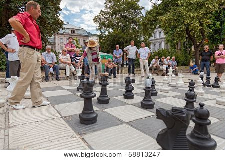 SARAJEVO, BOSNIA AND HERZEGOVINA - AUGUST 11, 2012: Men play chess on street with large chess pieces in the centre of Sarajevo. The game gathers men from all creed and religion.