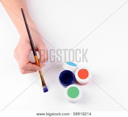 Hand holding brush with paints isolated on white