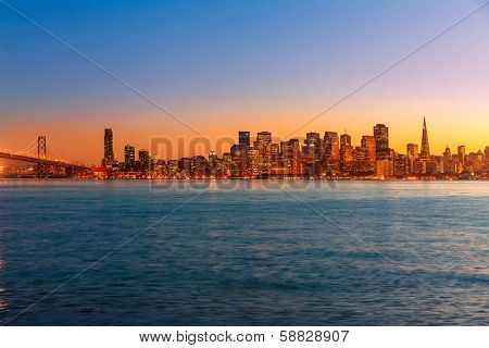 San Francisco sunset skyline in California with reflection in bay water USA