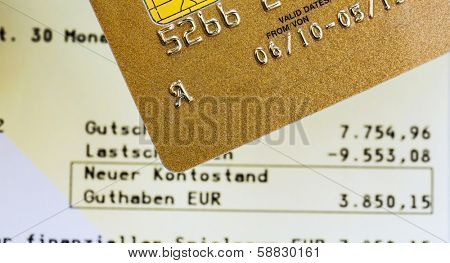 a golden credit card and bank statement .. symbolic photo for cashless purchases and status symbols.