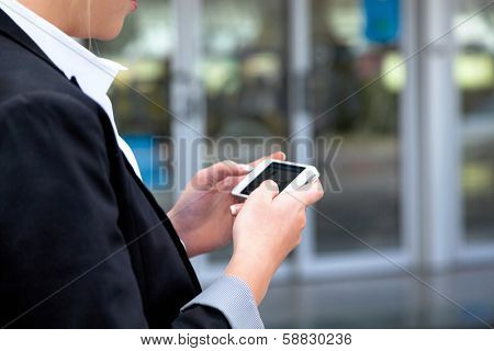 businesswoman writes on sms airport. roaming charges when abroad. accessibility with modern technology