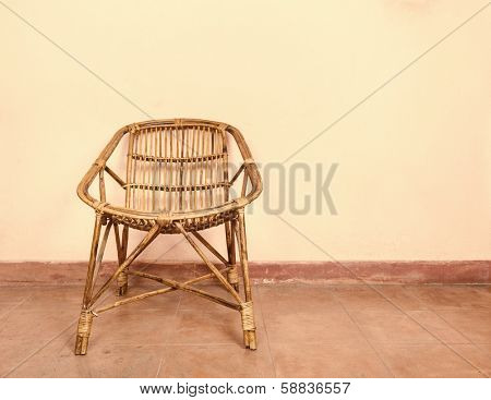 Wicker armchair and pink wall background