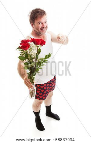 Scruffy looking guy in his underwear with too much confidence holding a vase of red roses and pointing at you. Full body isolated on white.