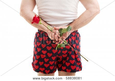 Rear view of a man in heart boxer shorts holding a red rose for his lover behind his back.  White background.