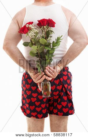 Rear view of man in heart boxers holding a bouquet of flowers behind his back.  White background.