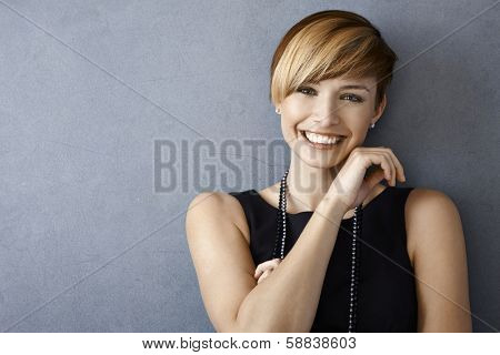 Closeup portrait of elegant young woman in black dress and pearls on grey background