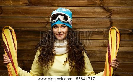 Smiling woman with skies standing against wooden house wall