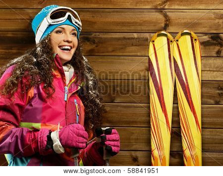 Smiling woman with skies and poles standing against wooden house wall