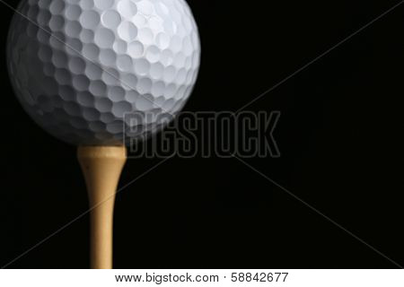Golf Ball Teed Up Close Up against a Black Background