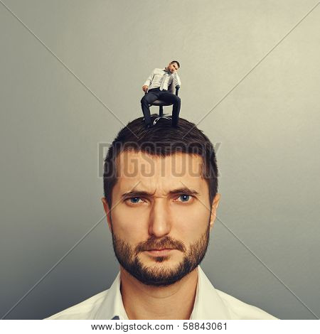 bored man sitting on the big head over grey background