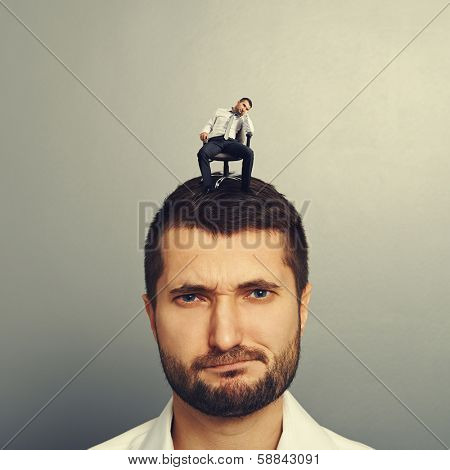 portrait of dissatisfied man with small bored man on the head