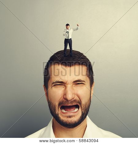 small angry boss standing on the head and screaming at worker
