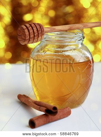 Honey with wood stick and cinnamon sticks