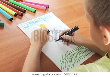 Child Draws Green Grass And Sun On Paper